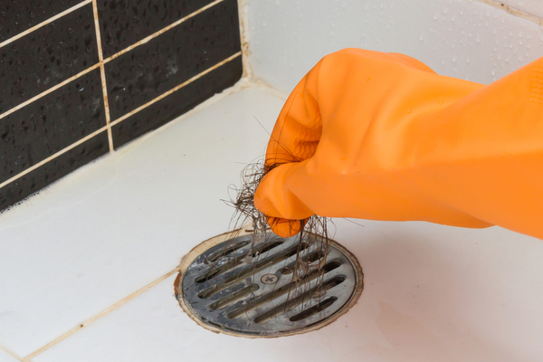 Gloved hand pulling hair out of a shower drain. Why does my shower drain smell?