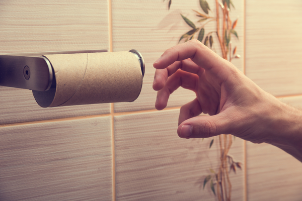 Hand reaching for used-up toilet paper roll