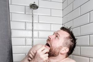 Homme à court d'eau chaude pendant une douche